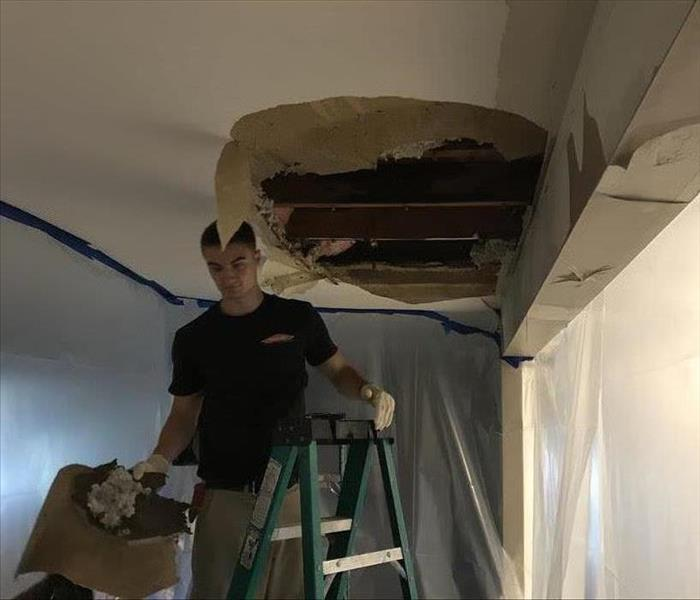 tech on a ladder removing water damaged ceiling sheetrock