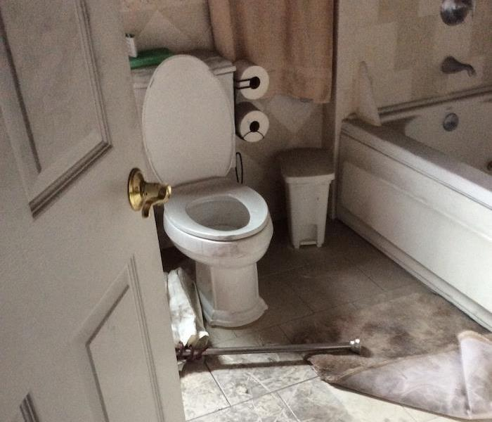 bathroom with smoke damaged toilet and floor