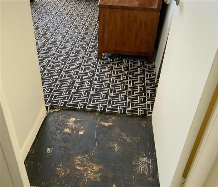 Room entrance with partially removed black and white carpet