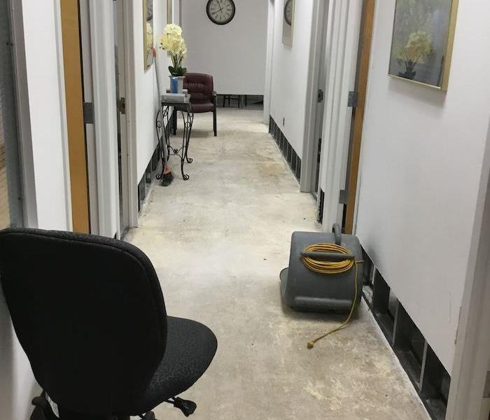 Office hallway with slab floor and SERVPRO drying equipment