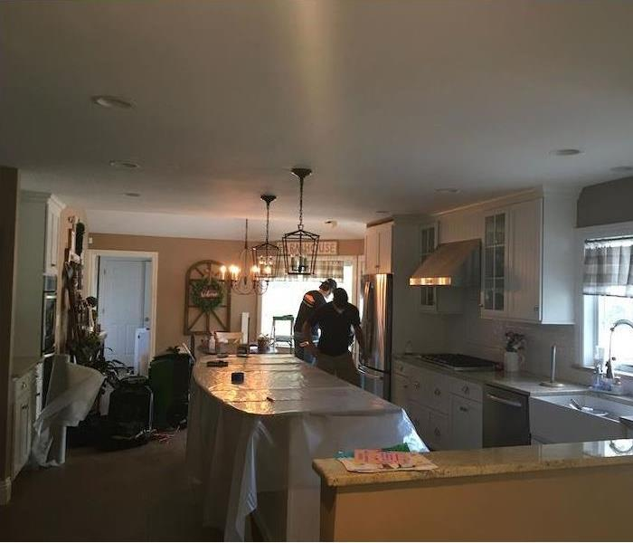 SERVPRO techs in kitchen with plastic-covered island