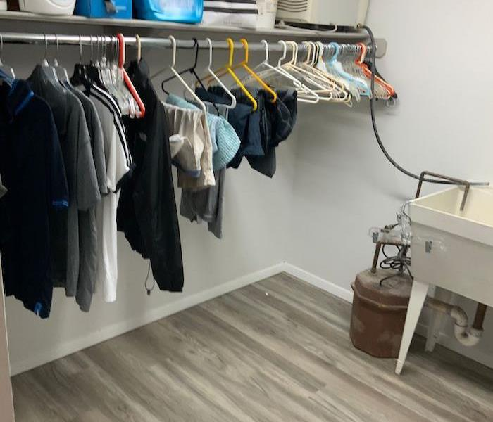 Room with items on hangers and missing baseboards