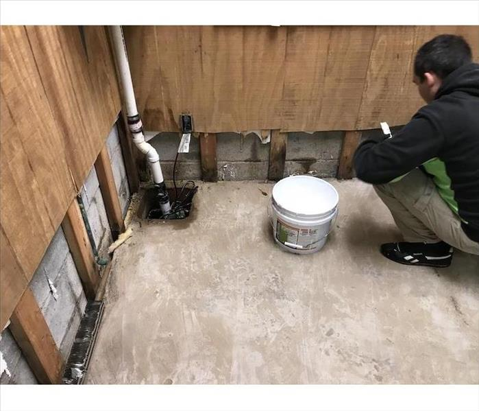 Basement with flood cuts on the walls and SERVPRO tech with equipment