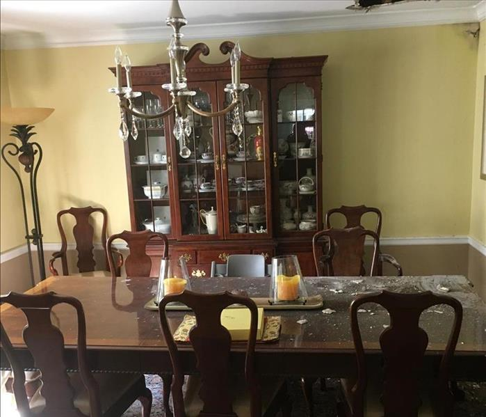 Dining room with furniture with a hole in the ceiling