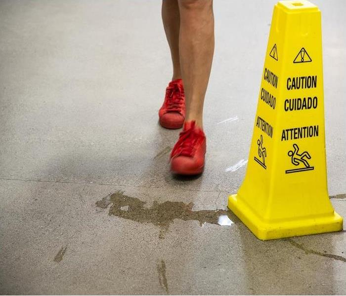 A woman about to step into a puddle of water in a commercial building