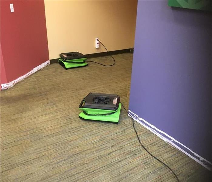 Green air movers drying out a room