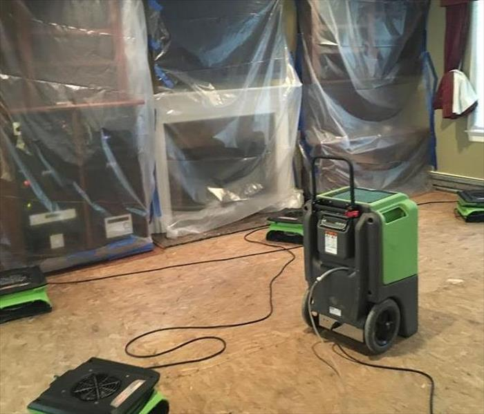 Furniture covered with plastic, with SERVPRO equipment on the floor.